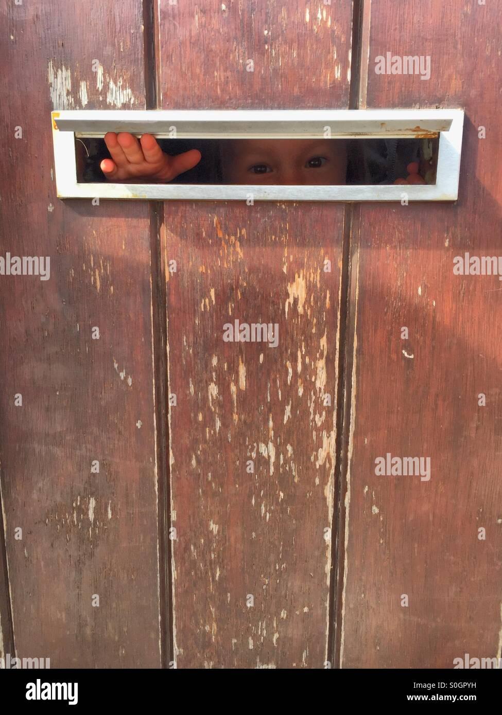 Little scared Child Peeking through the letterbox of a weathered door. & Little scared Child Peeking through the letterbox of a weathered ... Pezcame.Com