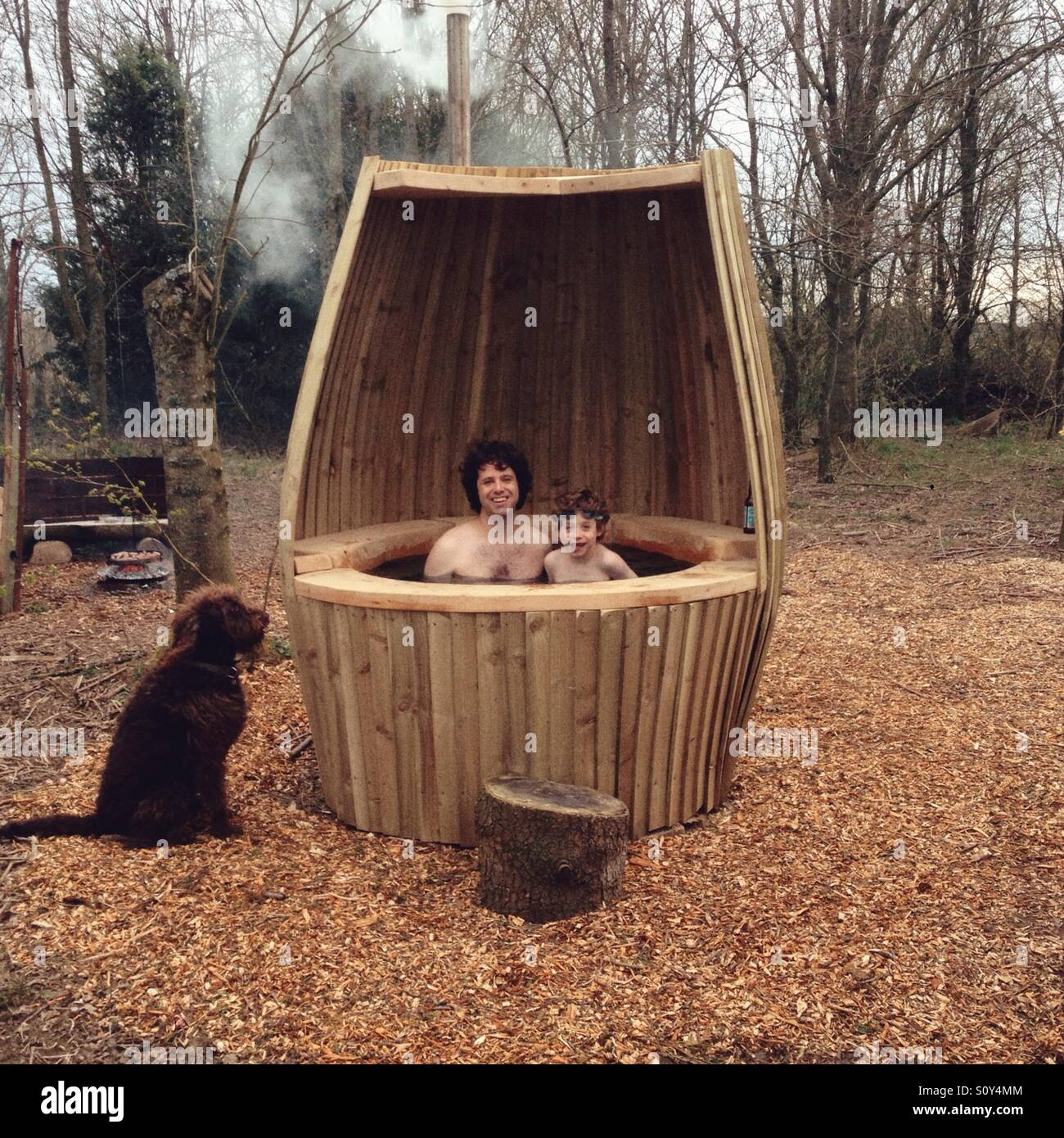Father And Son In A Outdoor Hot Tub Being Watched By A Labradoodle Dog.