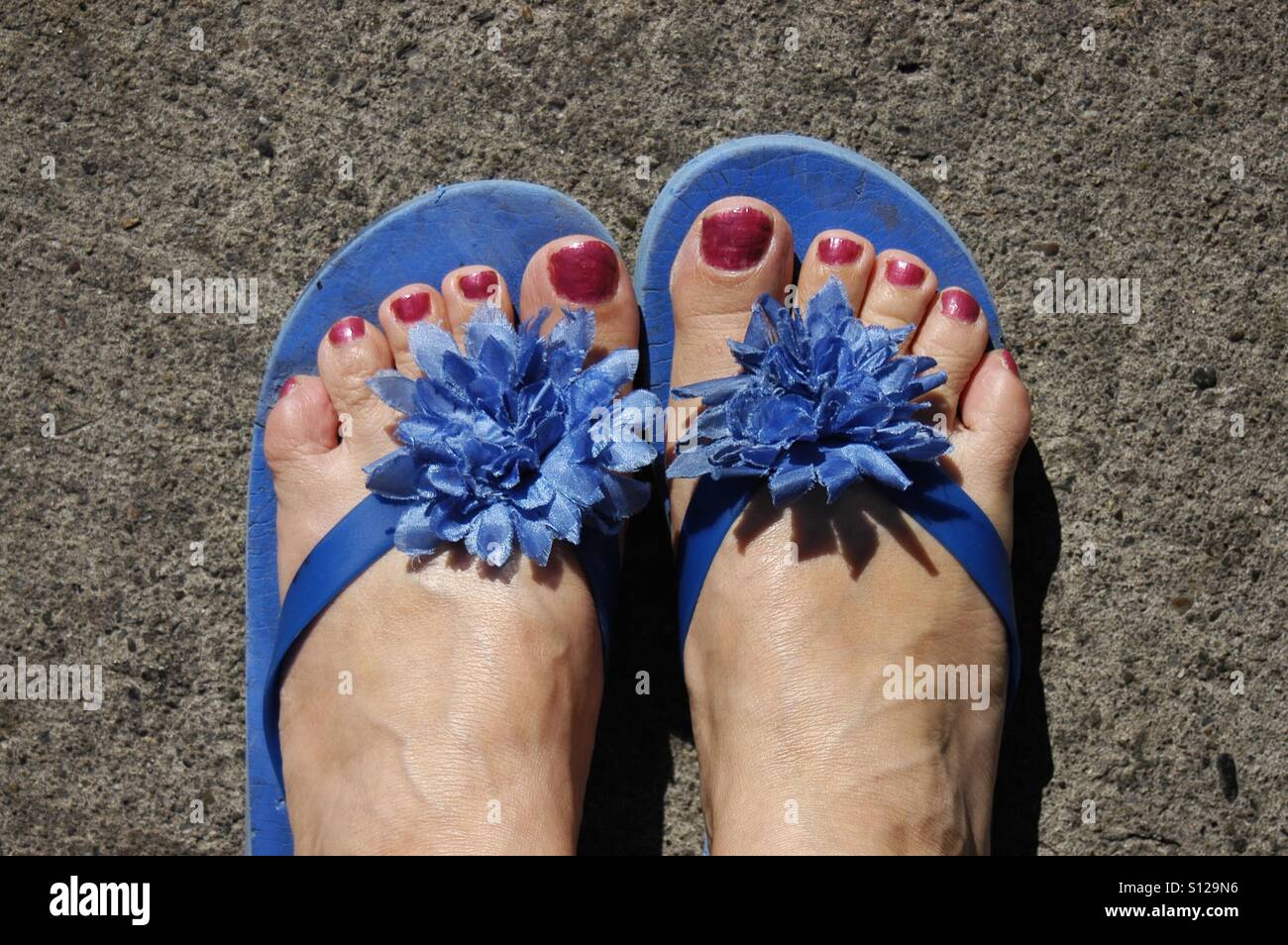blue flipflops with flower bow and feet with red painted toenails