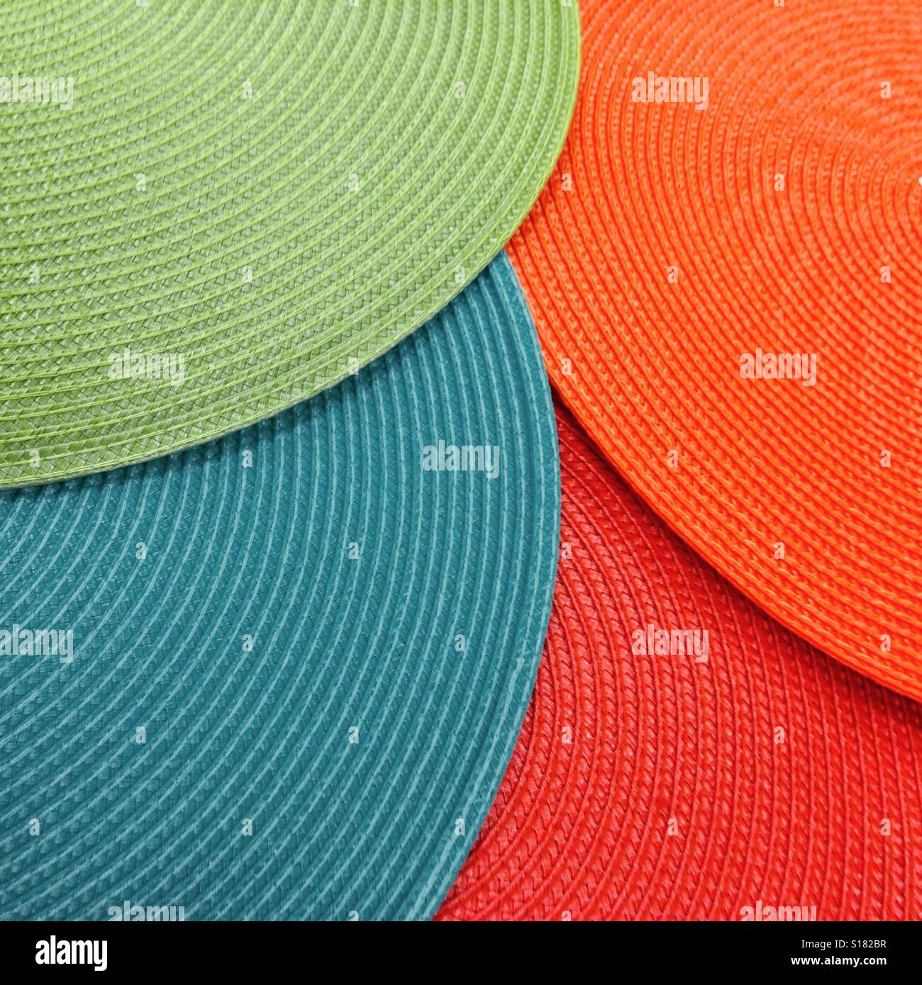 Colorful Round Woven Placemats Overlapping On A Table Top Stock