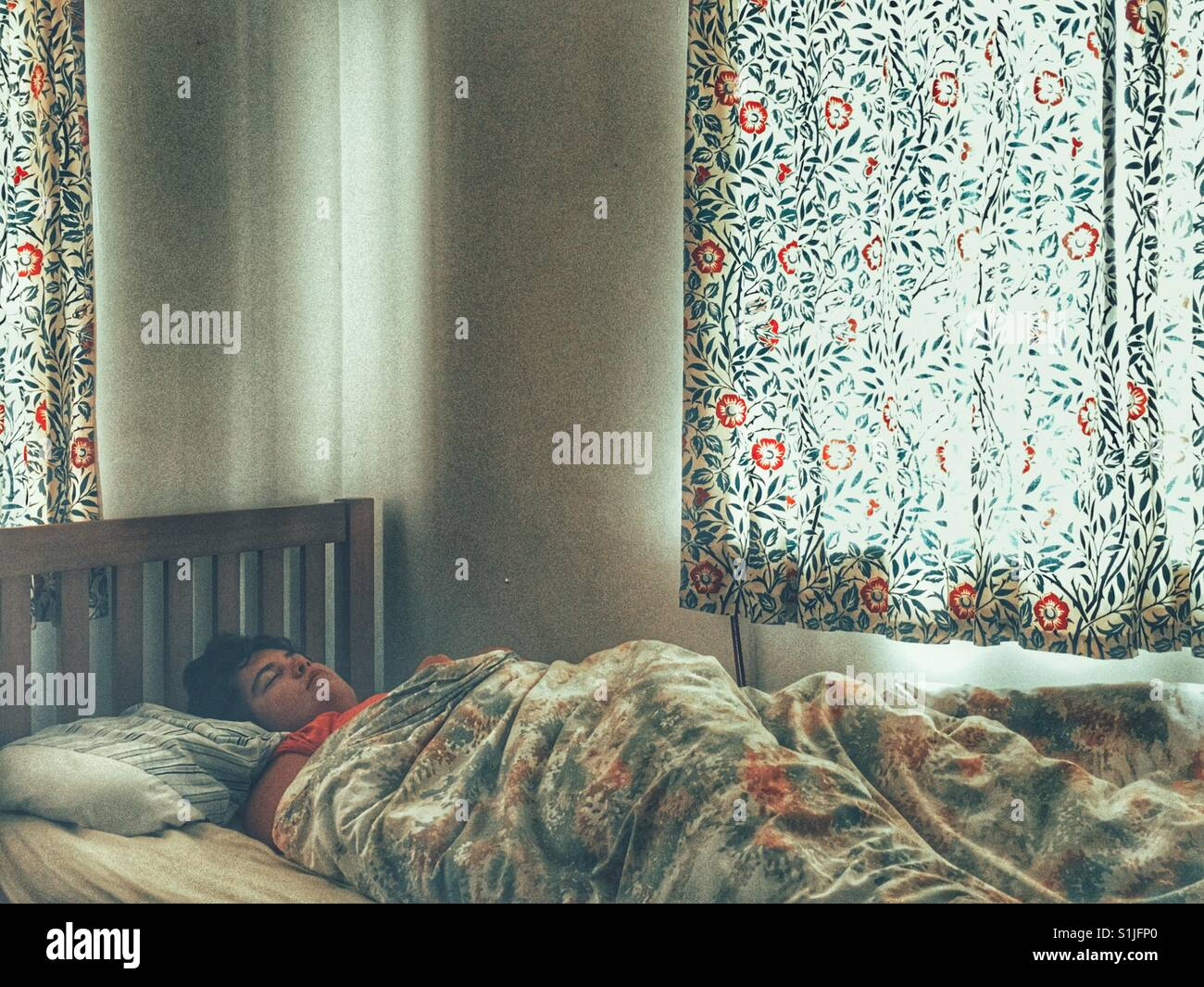 Young Woman Asleep In Bed With The Curtains Drawn, Daytime