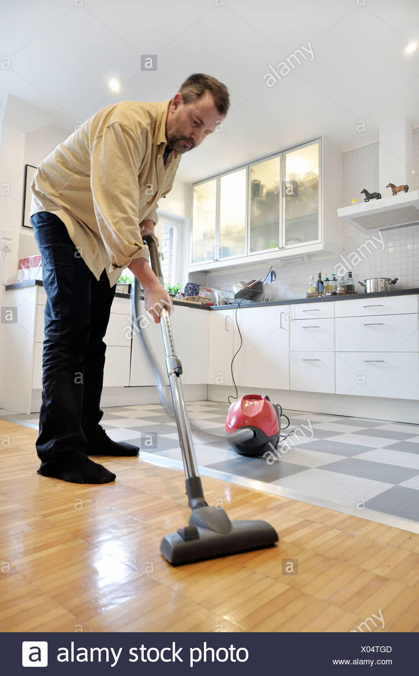 Middle Aged Man Using Vacuum Cleaner On The Wooden Floor With Kitchen In  The Background