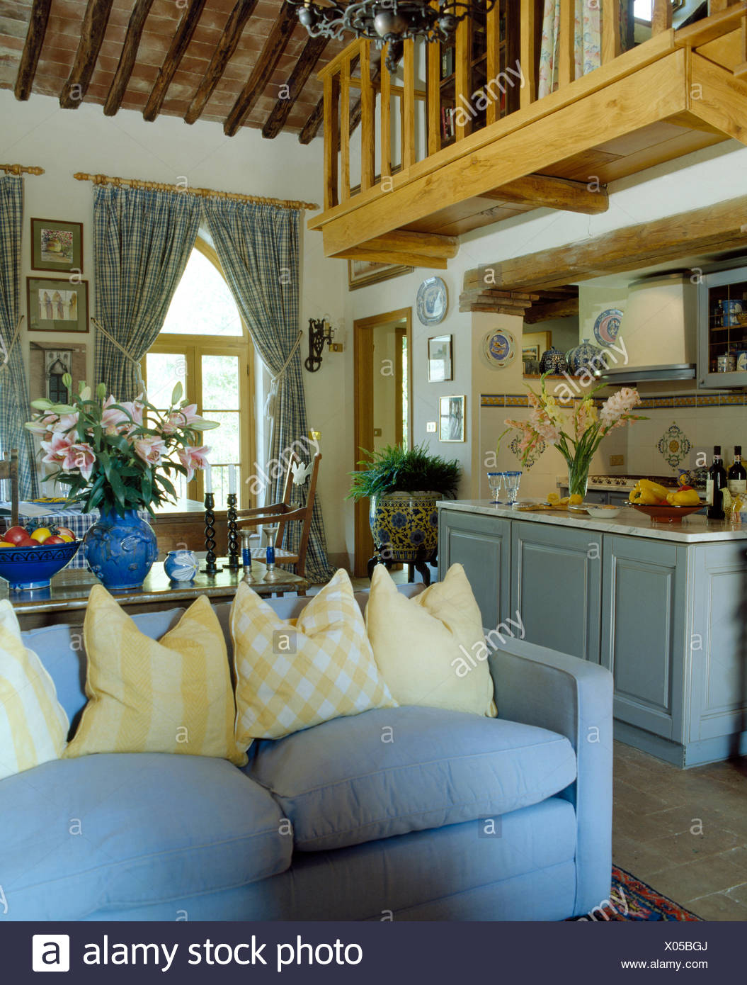 Yellow Cushions On Pale Blue Sofa In Open Plan Italian Living Room With  Mezzanine Balcony Above Kitchen
