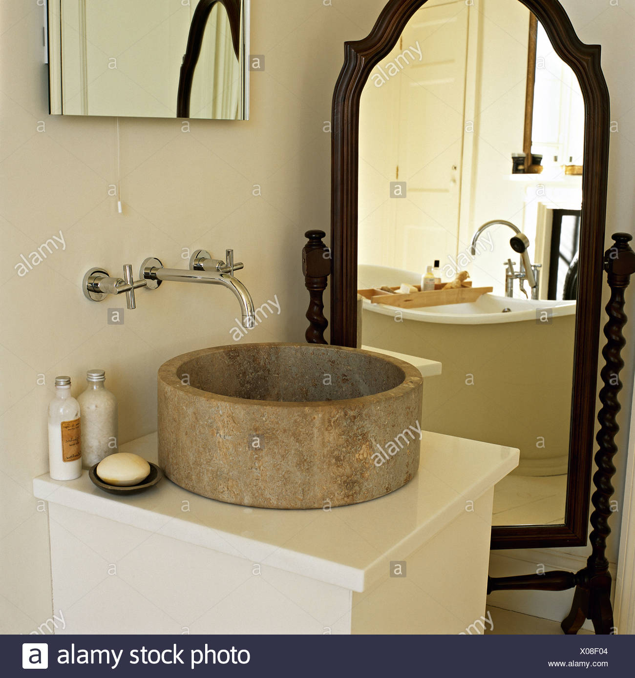 Wall mounted chrome tap above circular stone basin on simple vanity ...