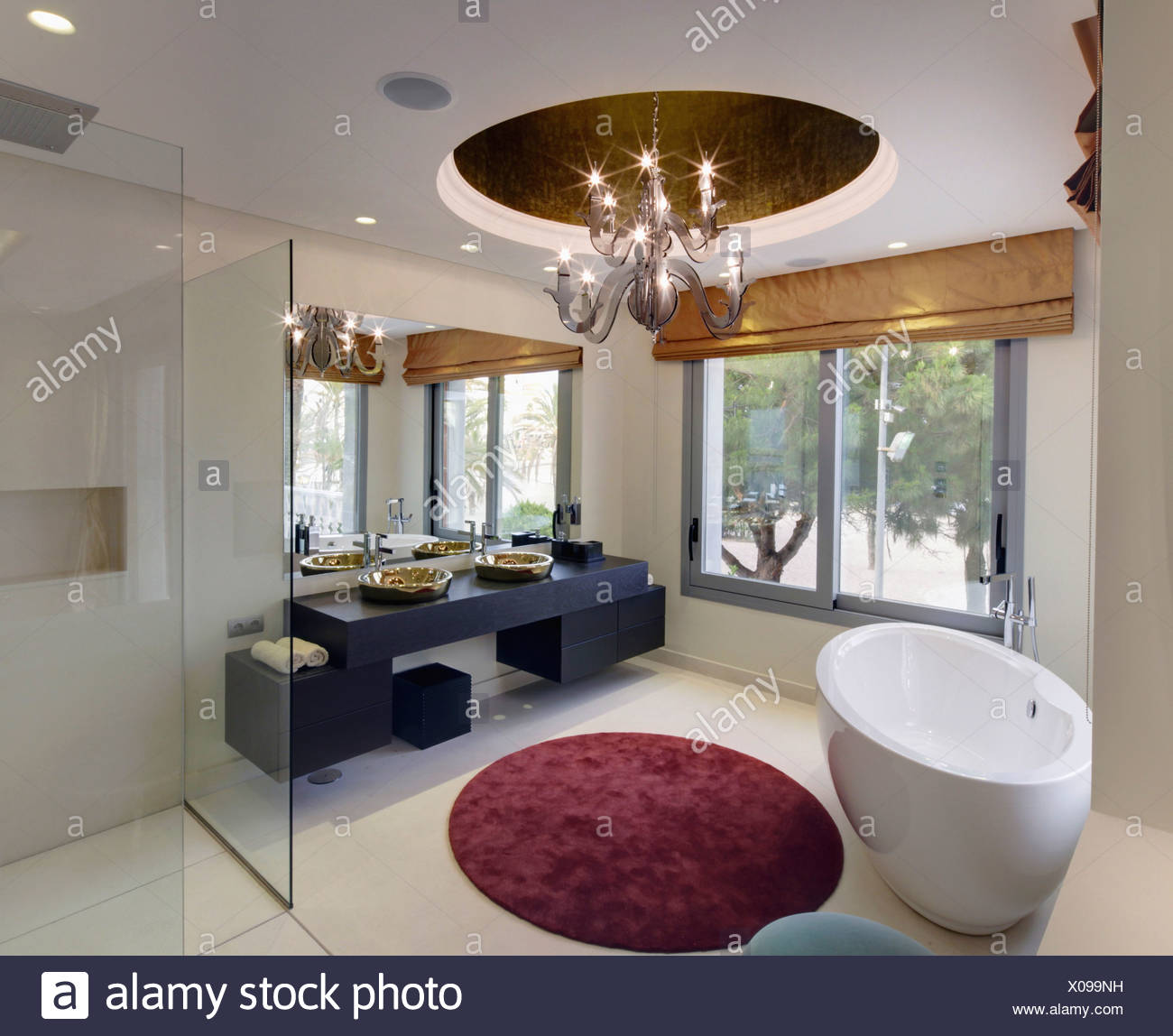 Oval Freestanding Bath And Circular Rug In Modern Bathroom With Central Light Fitting Large Windows