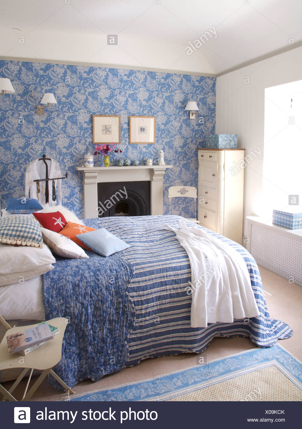Blue Striped Quilt With Floral Lining On Bed In Coastal Bedroom With