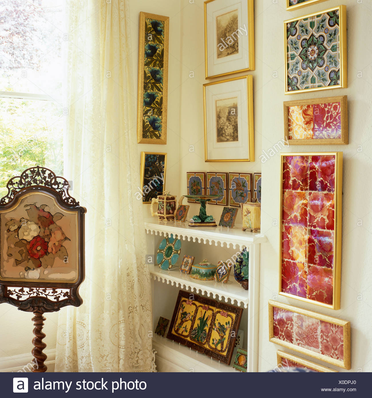 Antique tapestry screen on stand beside shelves beside colorful ...
