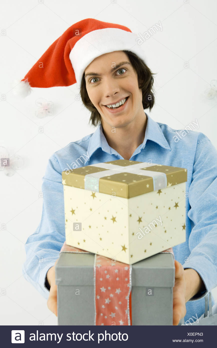 young man wearing santa hat holding out christmas gifts smiling at camera