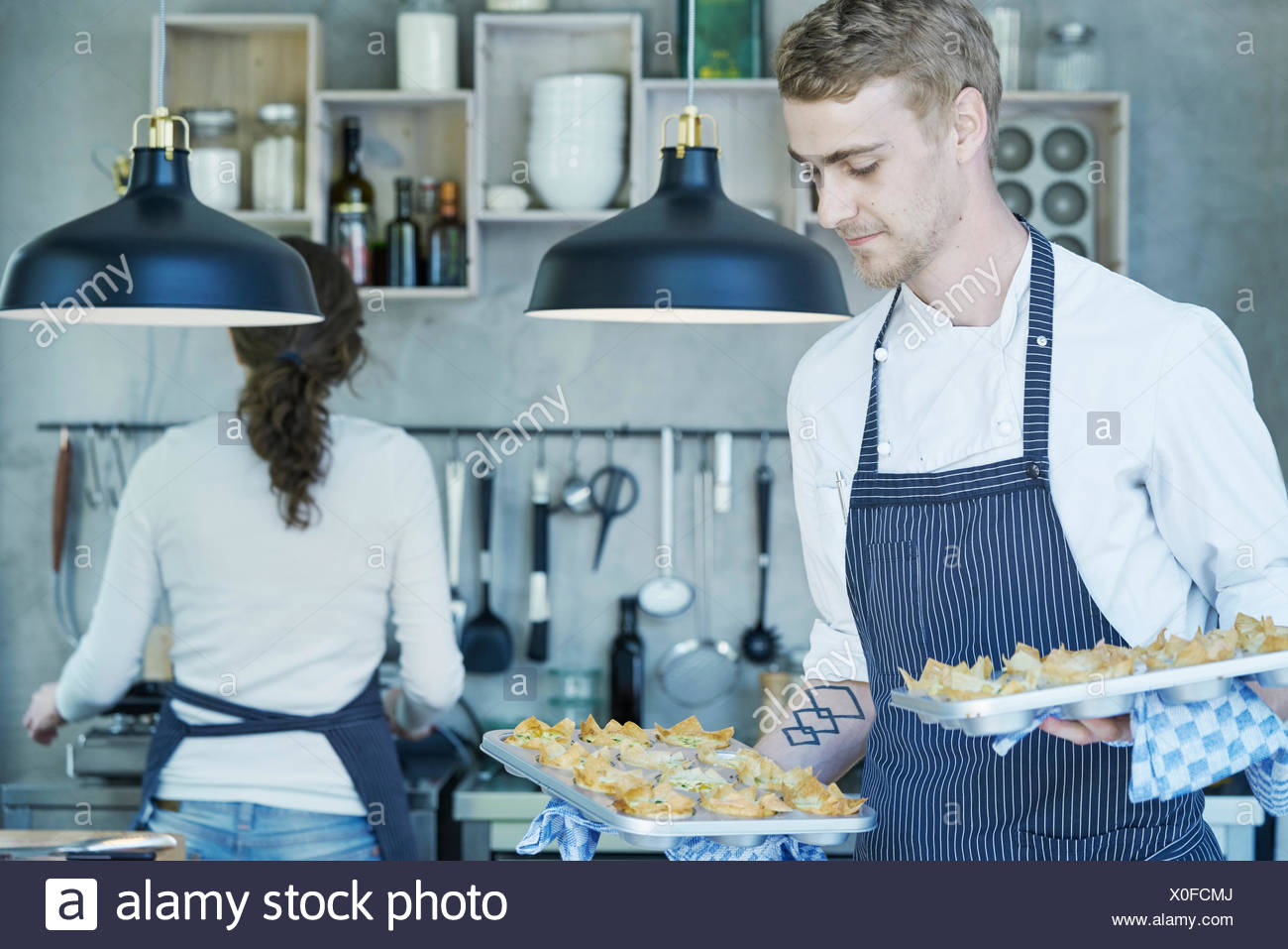 Chef in kitchen, holding baking trays of canapes Stock Photo ...
