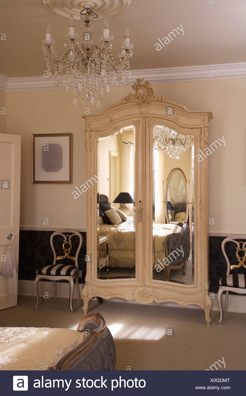 Striped Upholstered Chairs On Either Side Of French Style Wardrobe With Mirrored  Doors In Opulent Bedroom With Glass Chandelier