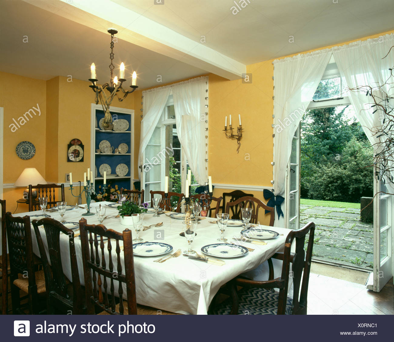 Yellow Dining Room With Table Settings And Open Door To Garden