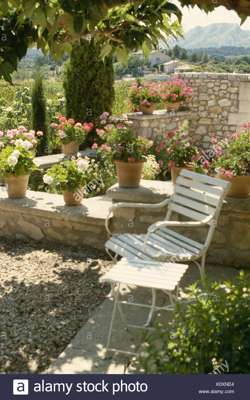 Shady gravel terrace with white garden chair and row of pink ...