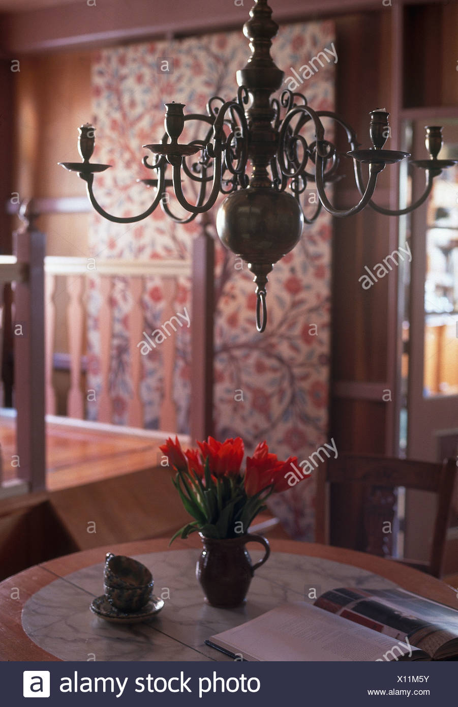Antique Brass Chandelier Above Table With Jug Of Red Tulips In Country Dining  Room