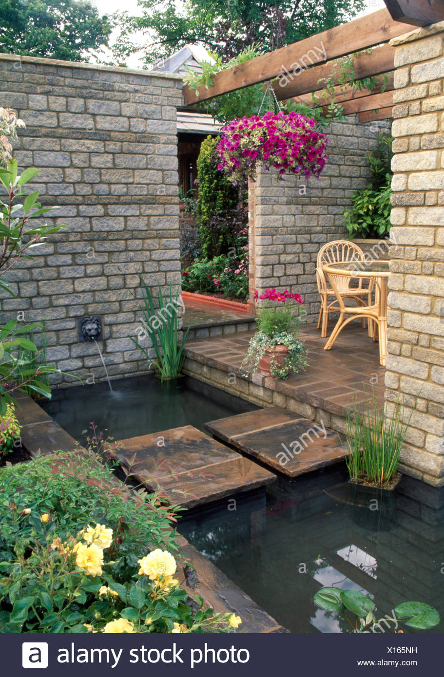 Pink Petunias In Hanging Basket Above Small Rectangular Pool Beside Brick  Patio With Stone Walls