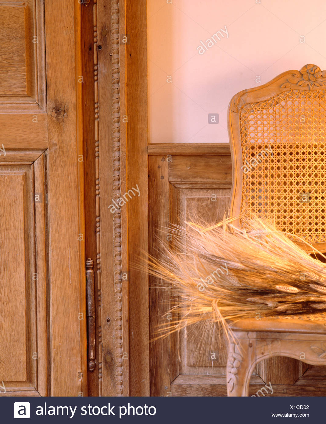 Close-up of dried grasses on antique cane and wood chair beside old French  door - Close-up Of Dried Grasses On Antique Cane And Wood Chair Beside Old