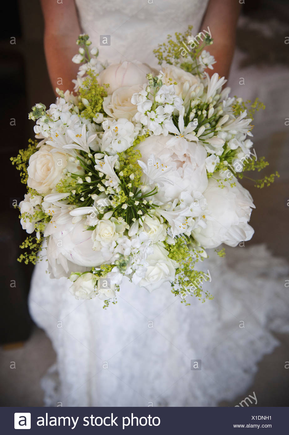 A bride holding a bridal bouquet of peonies and white flowers roses a bride holding a bridal bouquet of peonies and white flowers roses close up izmirmasajfo