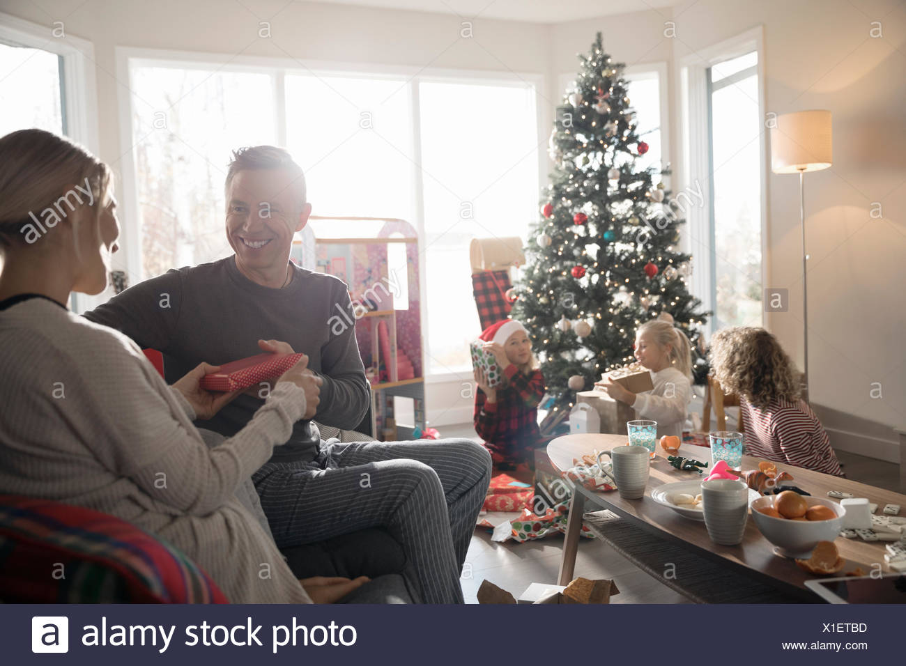 husband giving christmas gift to wife in living room with family