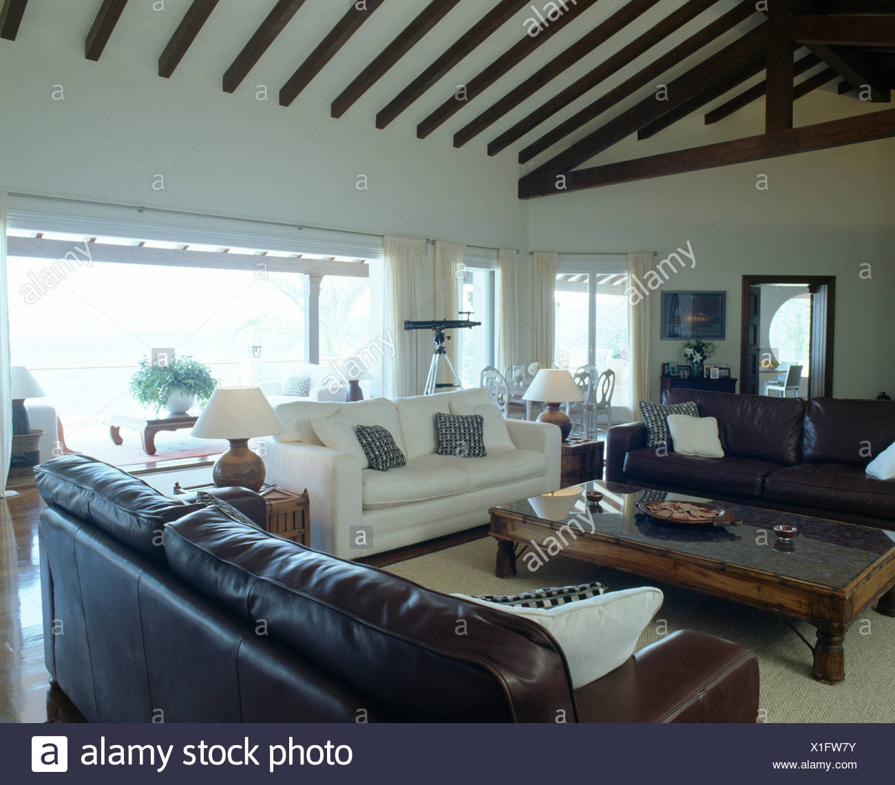 Brown Leather Sofas And White Sofa In Modern Coastal Living Room With  Indonesian Wood Coffee Table And Beamed Apex Ceiling