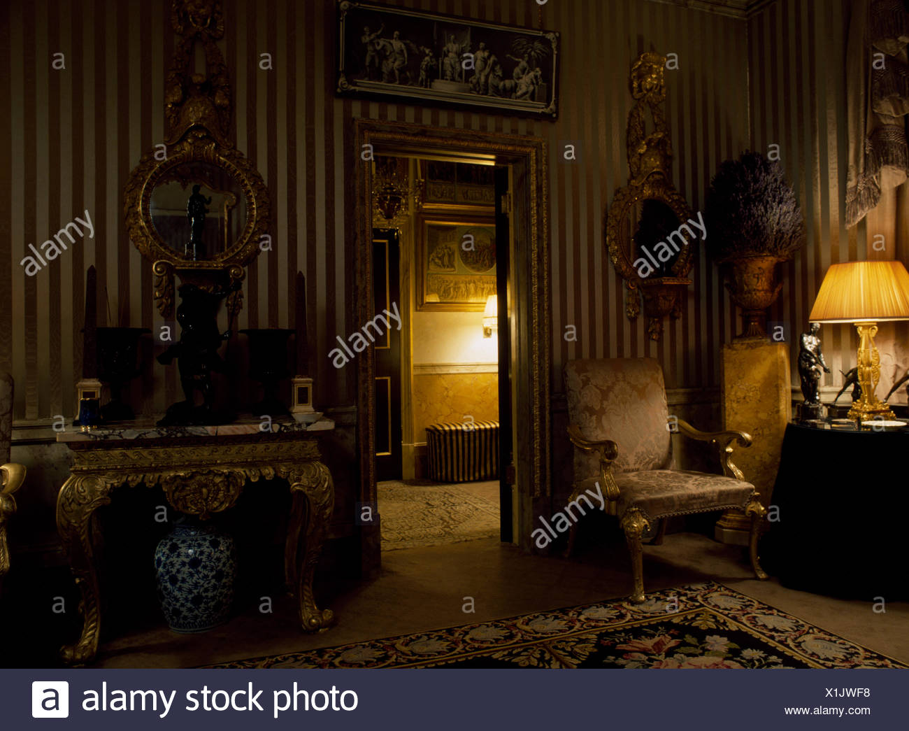 Antique Gilt Furniture And Striped Wallpaper In Regency Style Drawing Room