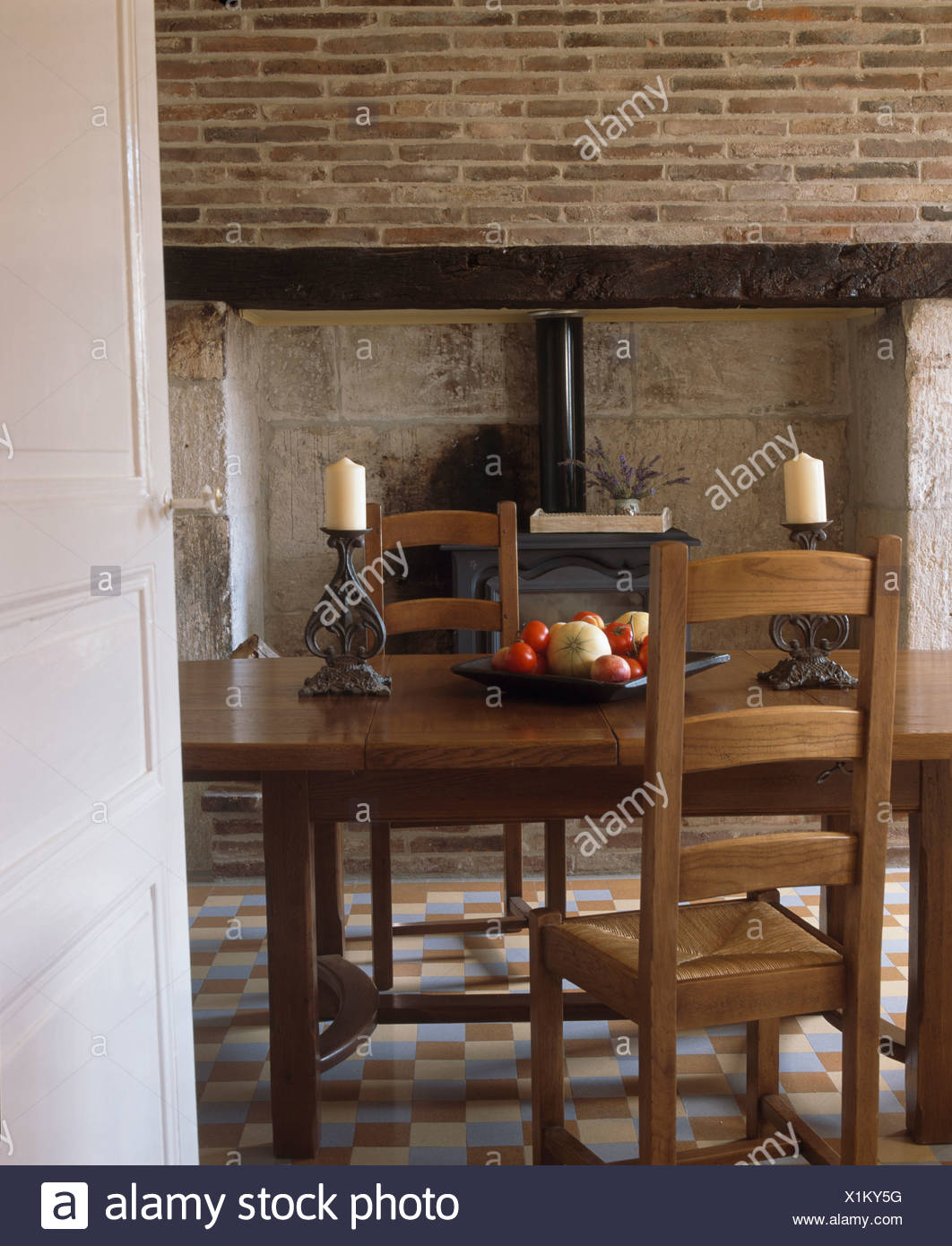 Rush Seated Ladder Back Chairs And Antique Table In French Country Dining  Room With Wood Burning Stove In The Fireplace