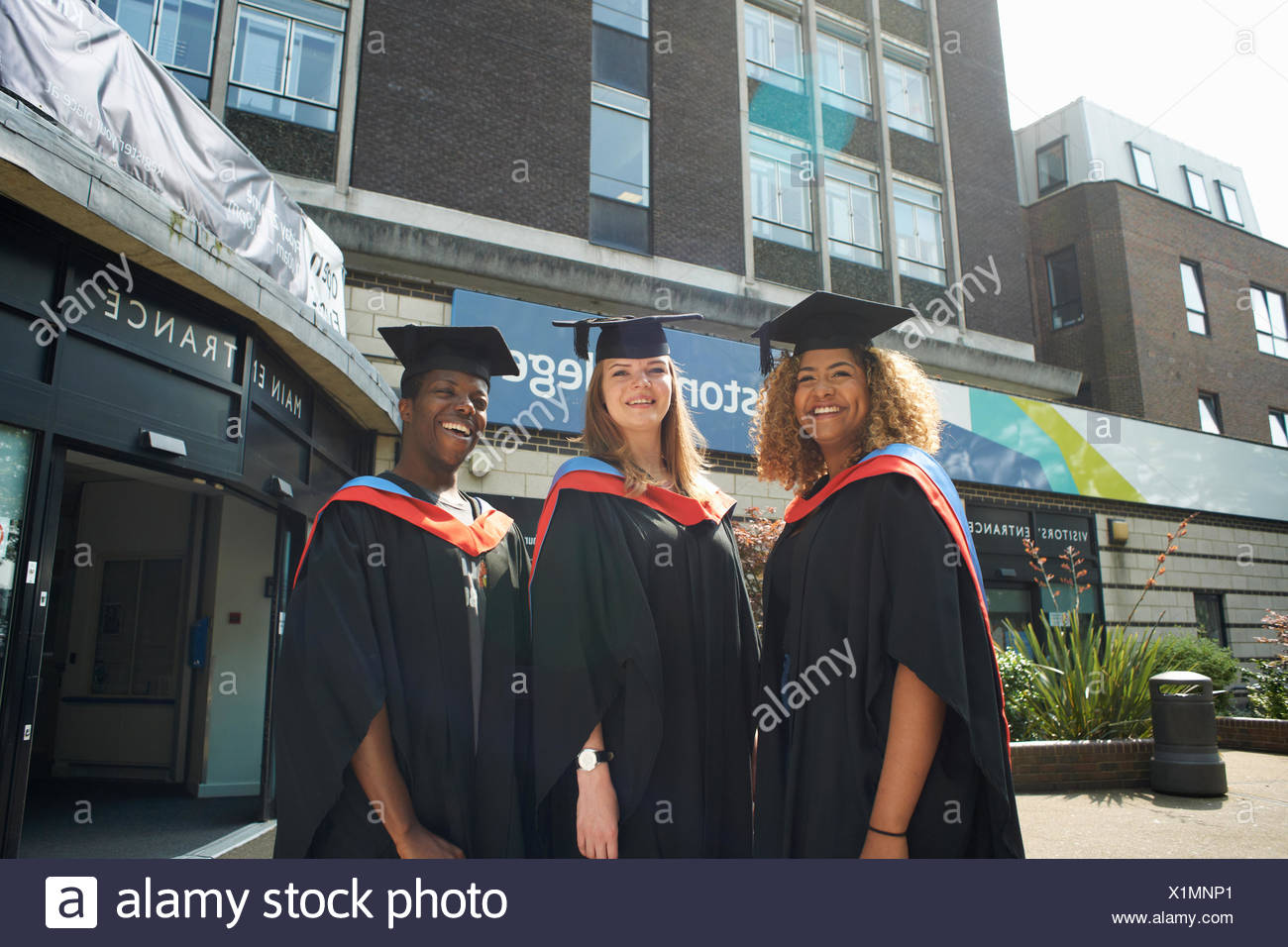 Portrait of three college students in graduation gowns and caps ...