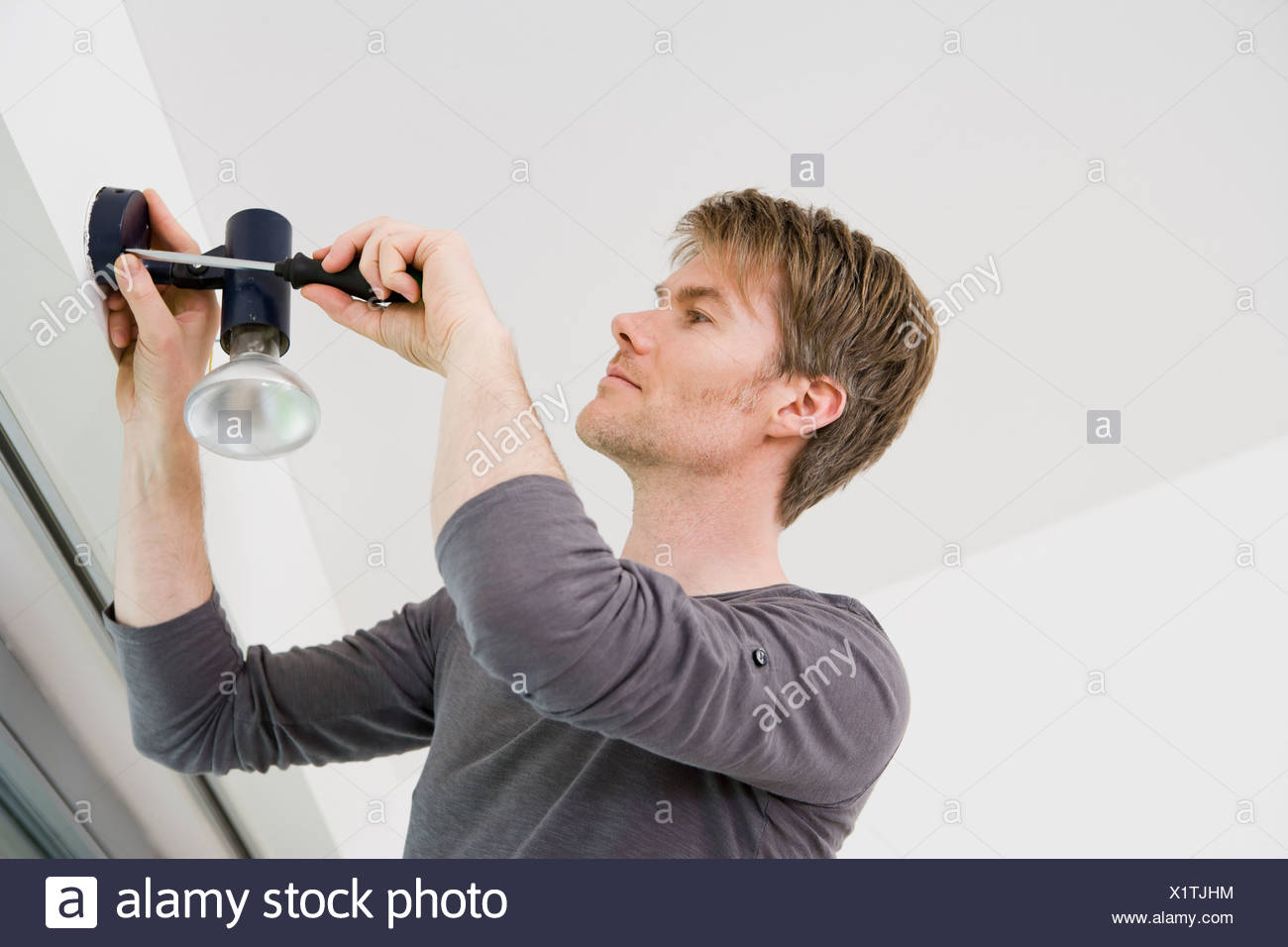 Man Installing Light Fixture In House Stock Photo 276522000 Alamy Basic Household Wiring