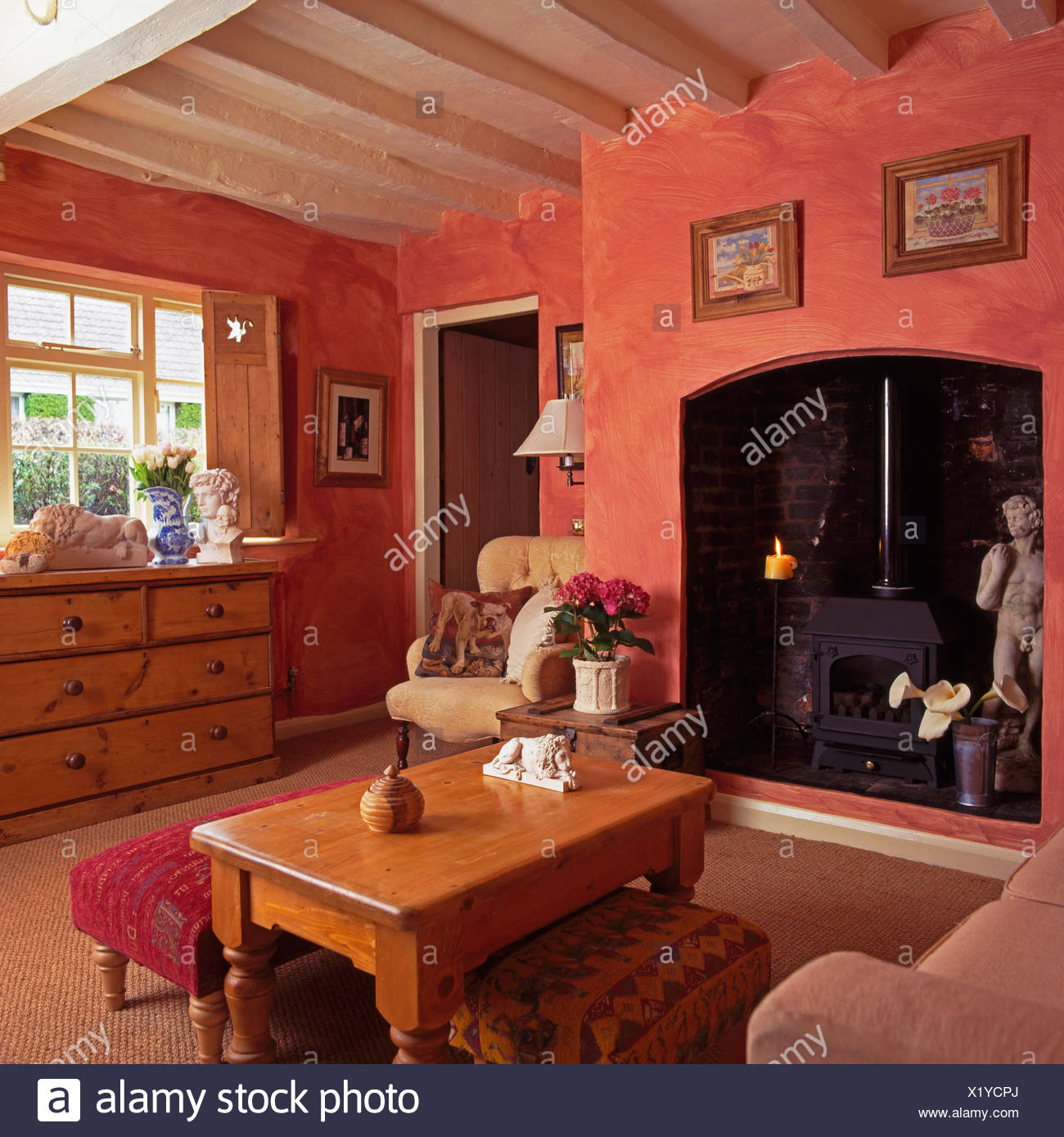 Upholstered stools and pine coffee table in terracotta pink cottage living room with wood burning stove in fireplace