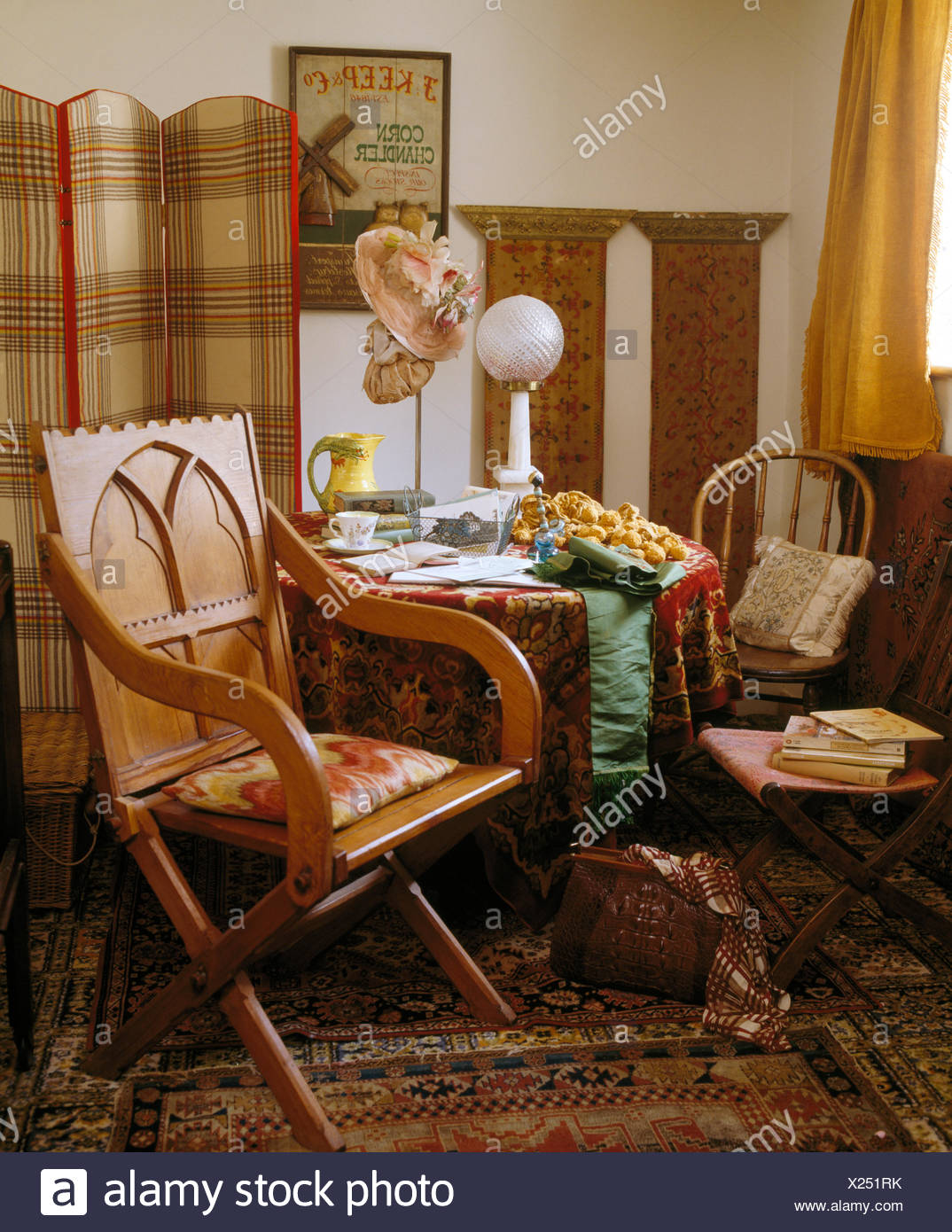 Antique chair and small table with richly patterned cloth in front of  screen in corner of dining room - Antique Chair And Small Table With Richly Patterned Cloth In Front