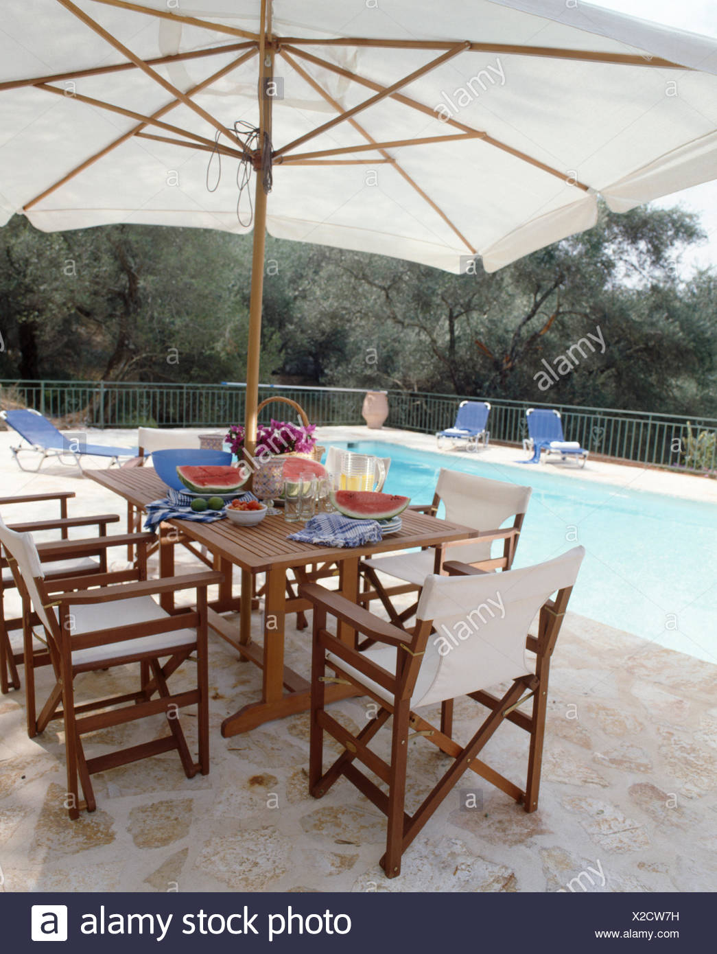 White Directoru0027s Chairs And Wooden Table Below Large White Umbrella On  Paving Beside Swimming Pool On Corfu
