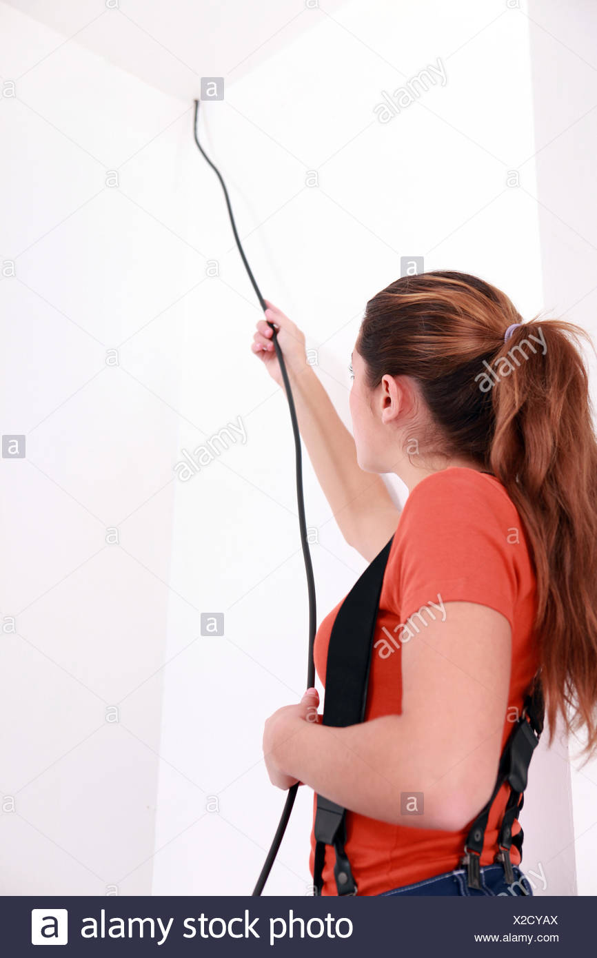 handywoman pulling a black wire coming from the ceiling Stock Photo ...