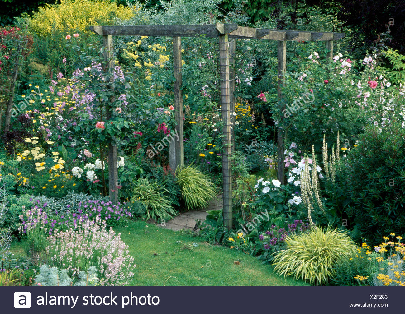 Rustic wooden pergola above paving between well stocked borders with rustic wooden pergola above paving between well stocked borders with grasses and yellow and white flowering summer plants mightylinksfo