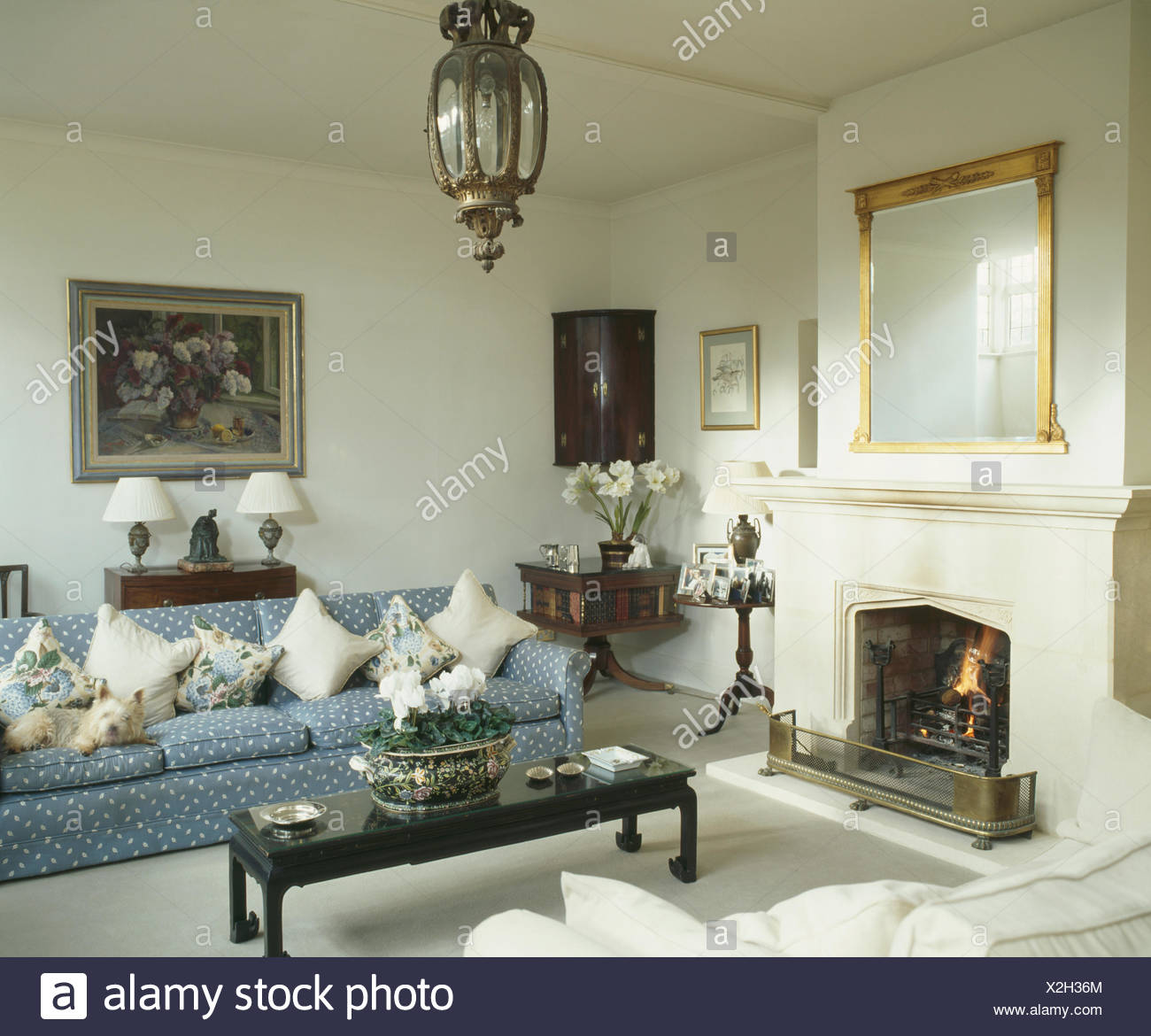 Beau Cream Cushions On Patterned Blue Sofa In Cream Living Room With Fireplace  And Brass Lantern