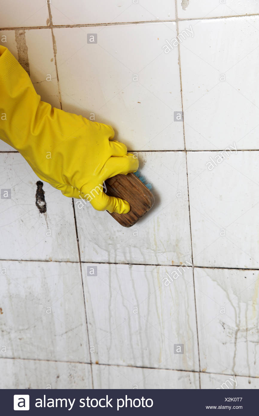 gloved hand cleaning dirty old tiles with brush in a bathroom Stock ...