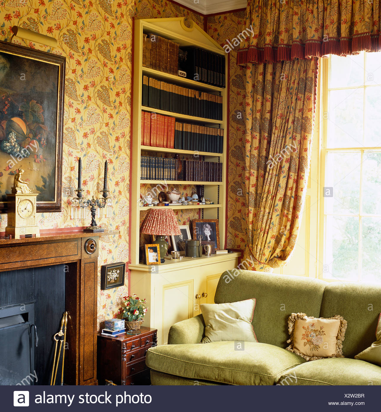Floral Curtains And Pedimented Alcove Bookcase Behind Sofa Next To  Fireplace In Country Living Room With Floral Wallpaper