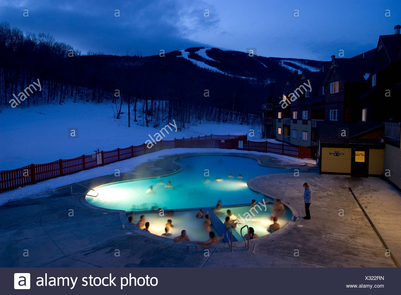 Skiers relax in a heated pool and hot tub at a hotel at Sunday River ...