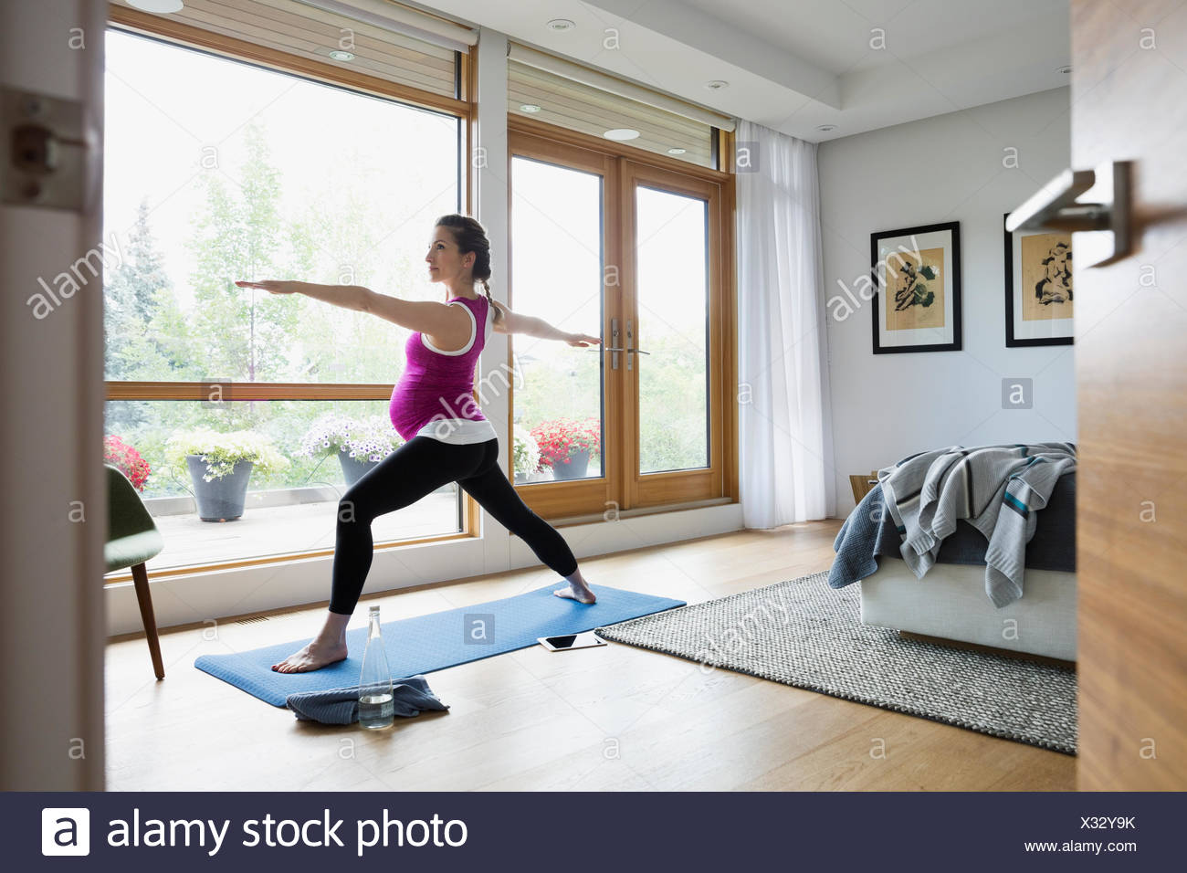 Pregnant Woman Practicing Warrior 2 Yoga Pose In Bedroom