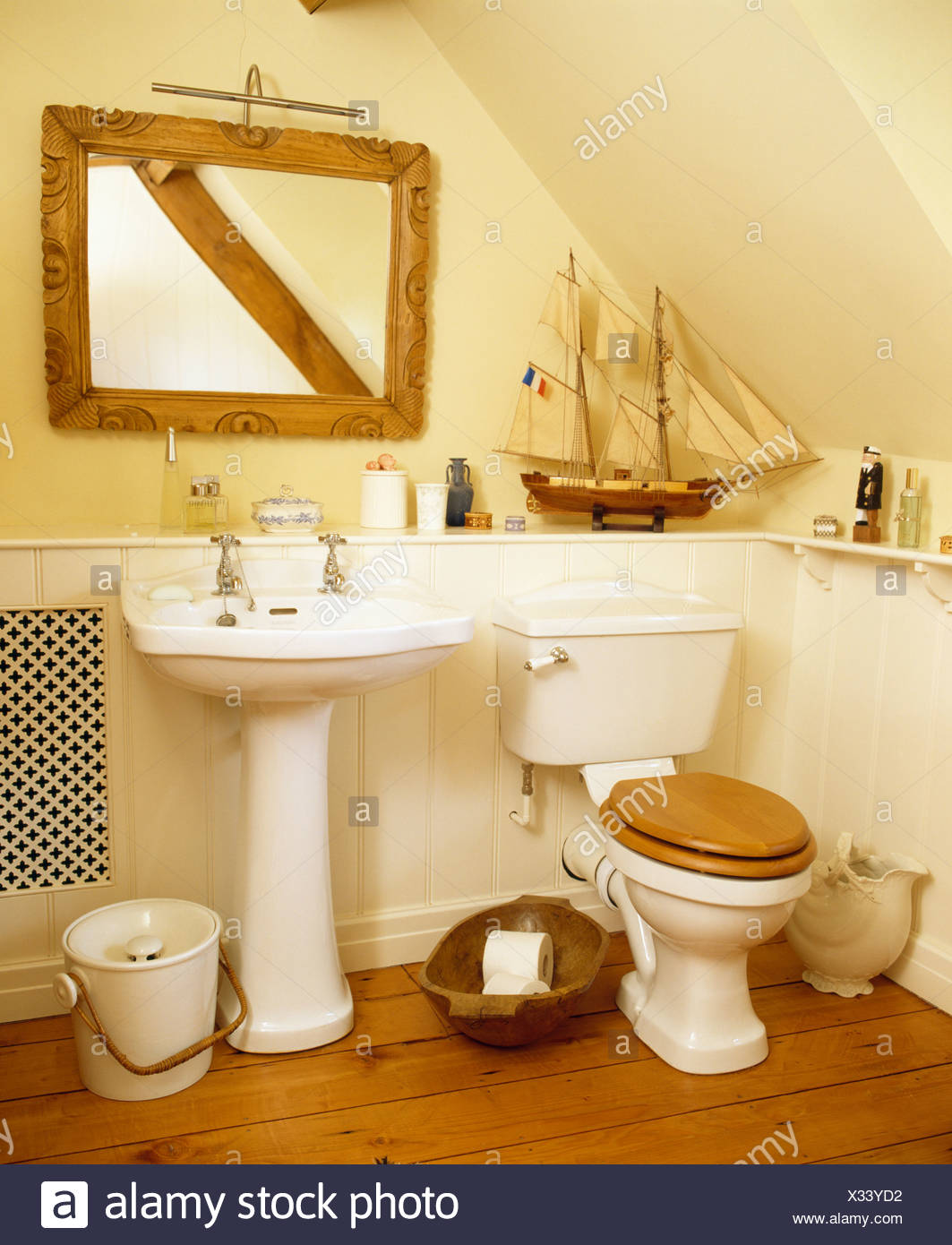 Wooden Framed Mirror Above White Pedestal Basin In Cottage Bathroom With  Model Sailing Boat On Shelf Above Toilet