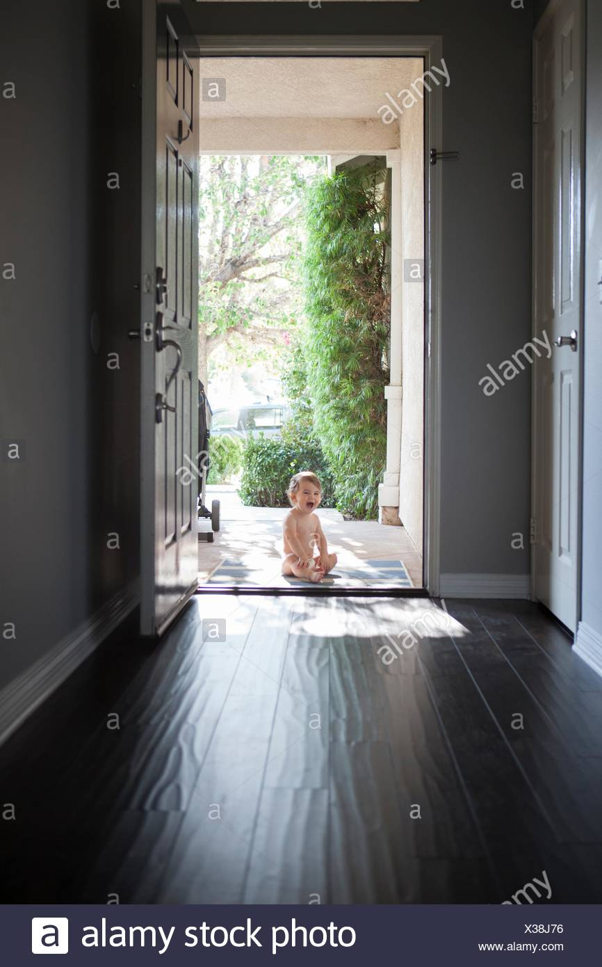 View Through Entrance Hall Of Baby Boy Sitting Outside At Open Front