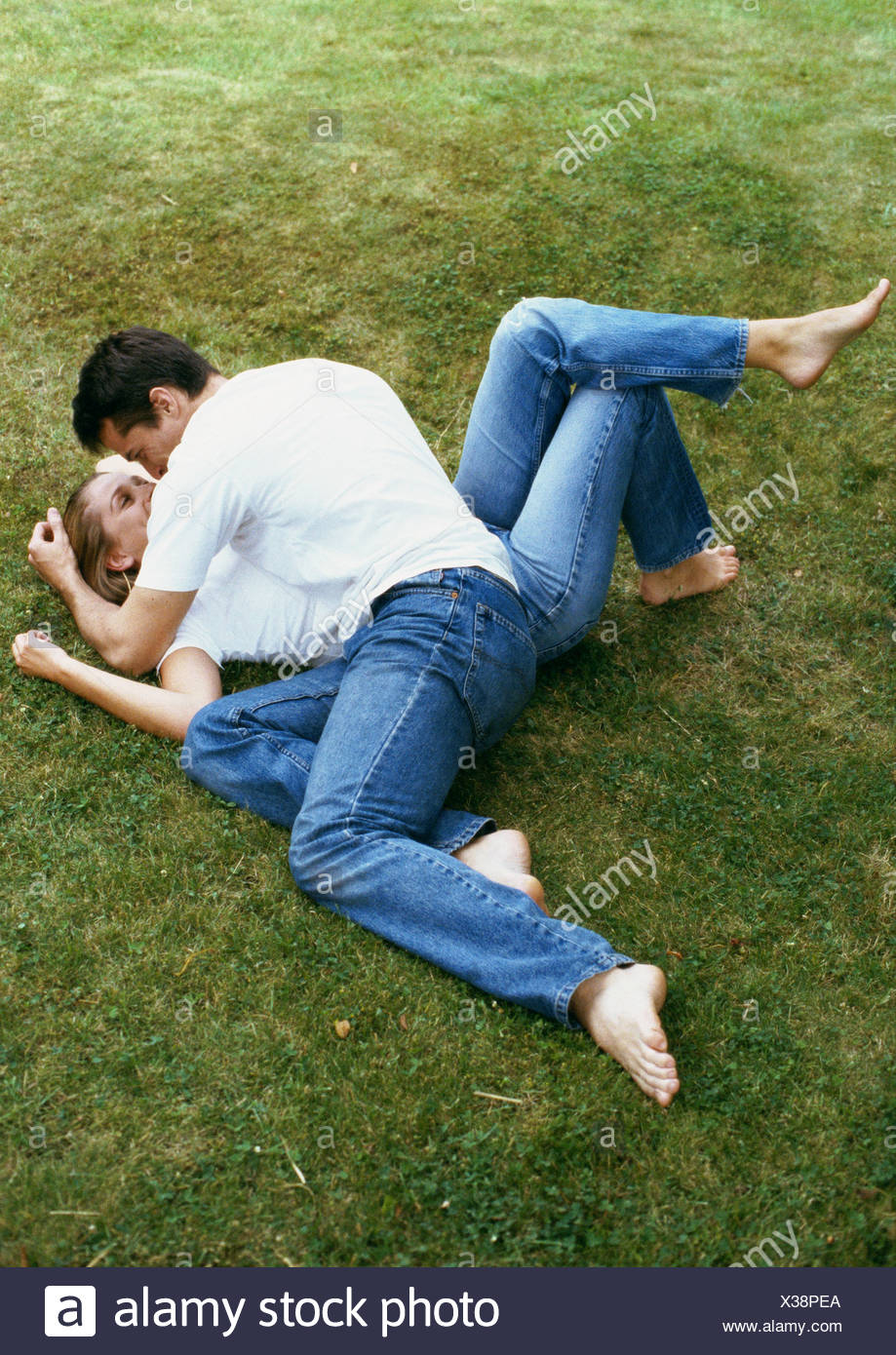 couple lying on grass man leaning over woman stock photo 277403122