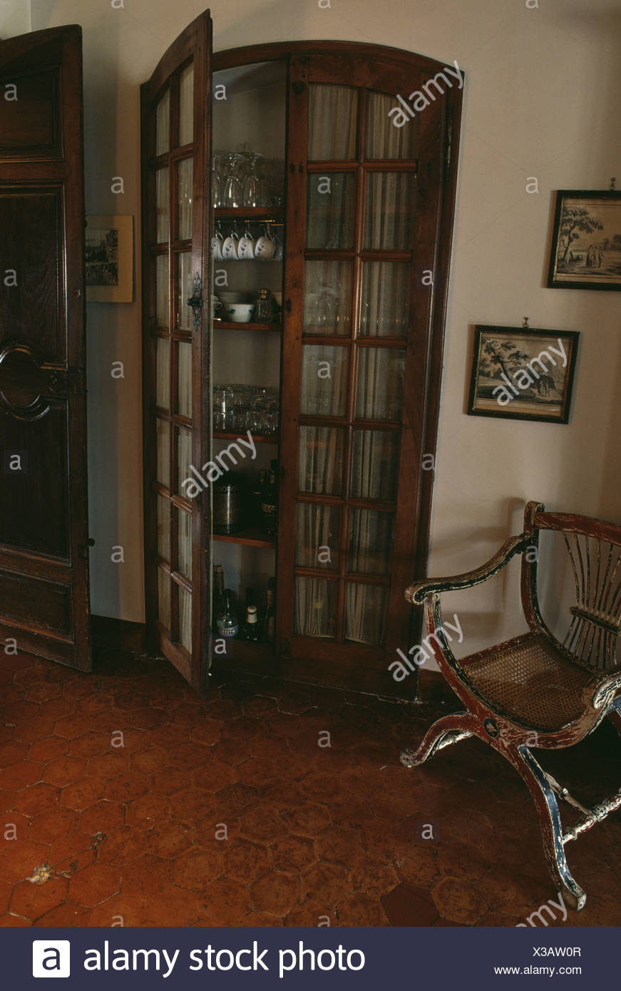 China and glasses stored in antique cupboard with glazed doors in  traditional country hall - China And Glasses Stored In Antique Cupboard With Glazed Doors In