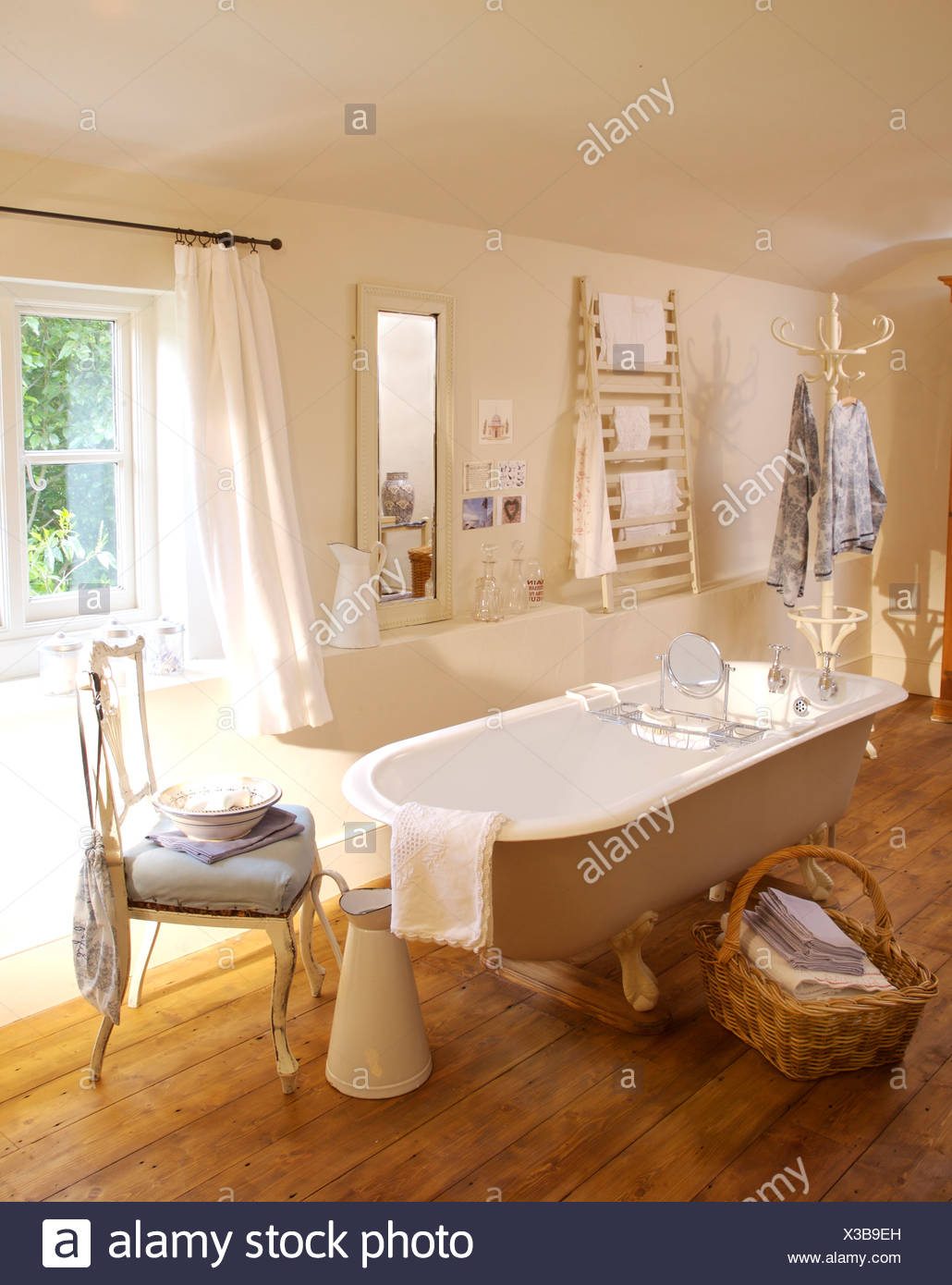 Towels In Large Basket Beside Roll Top Bath In Country Bathroom With Wooden  Floor And White Chair