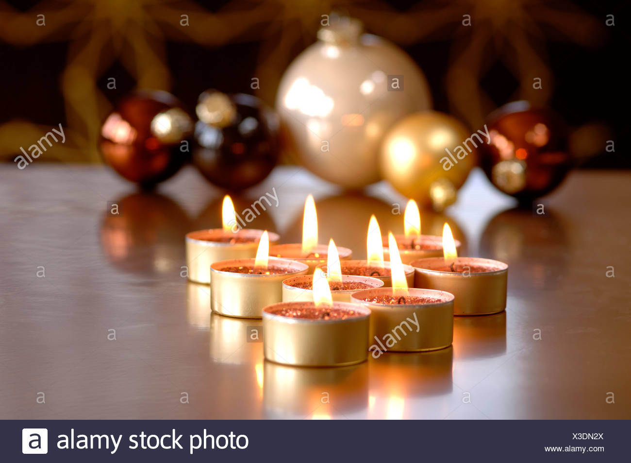 christmas baubles and burning tea lights