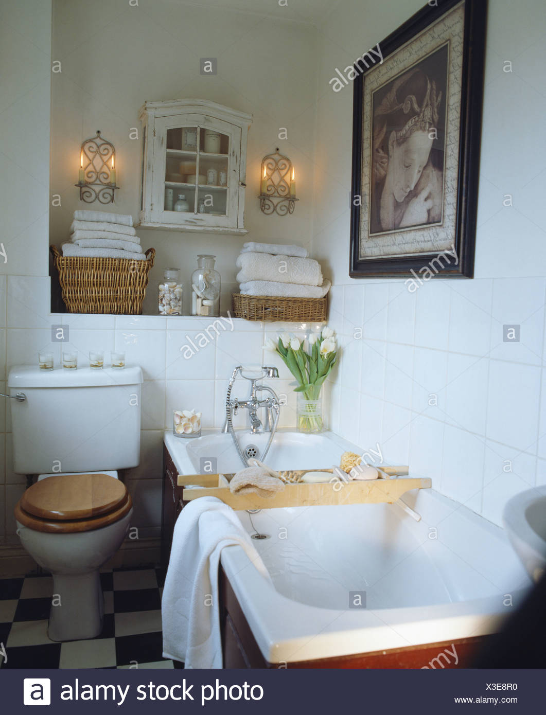 Wood rack across bath in white tiled country bathroom with wall ...