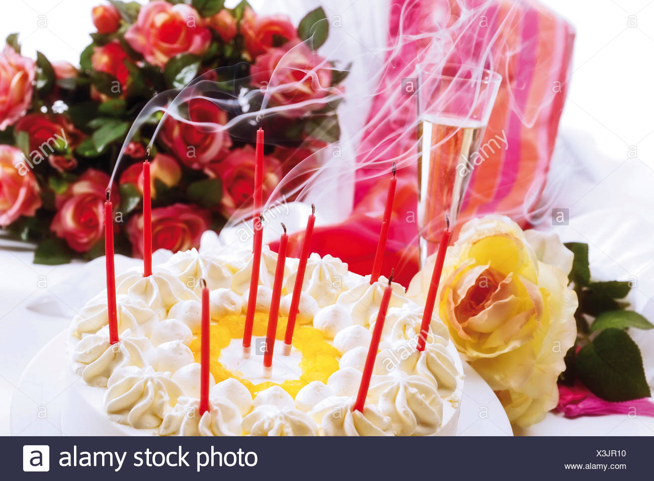 Blown out candles on a birthday cake bouquet of roses and a gift in blown out candles on a birthday cake bouquet of roses and a gift in the background izmirmasajfo