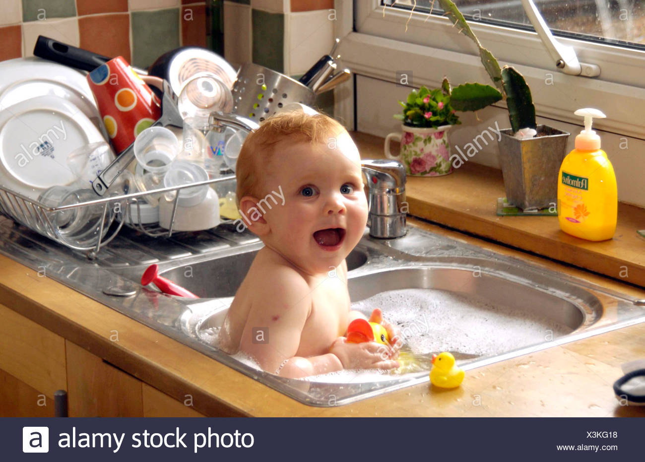 Female child sitting in kitchen sink full of soapy water holding ...