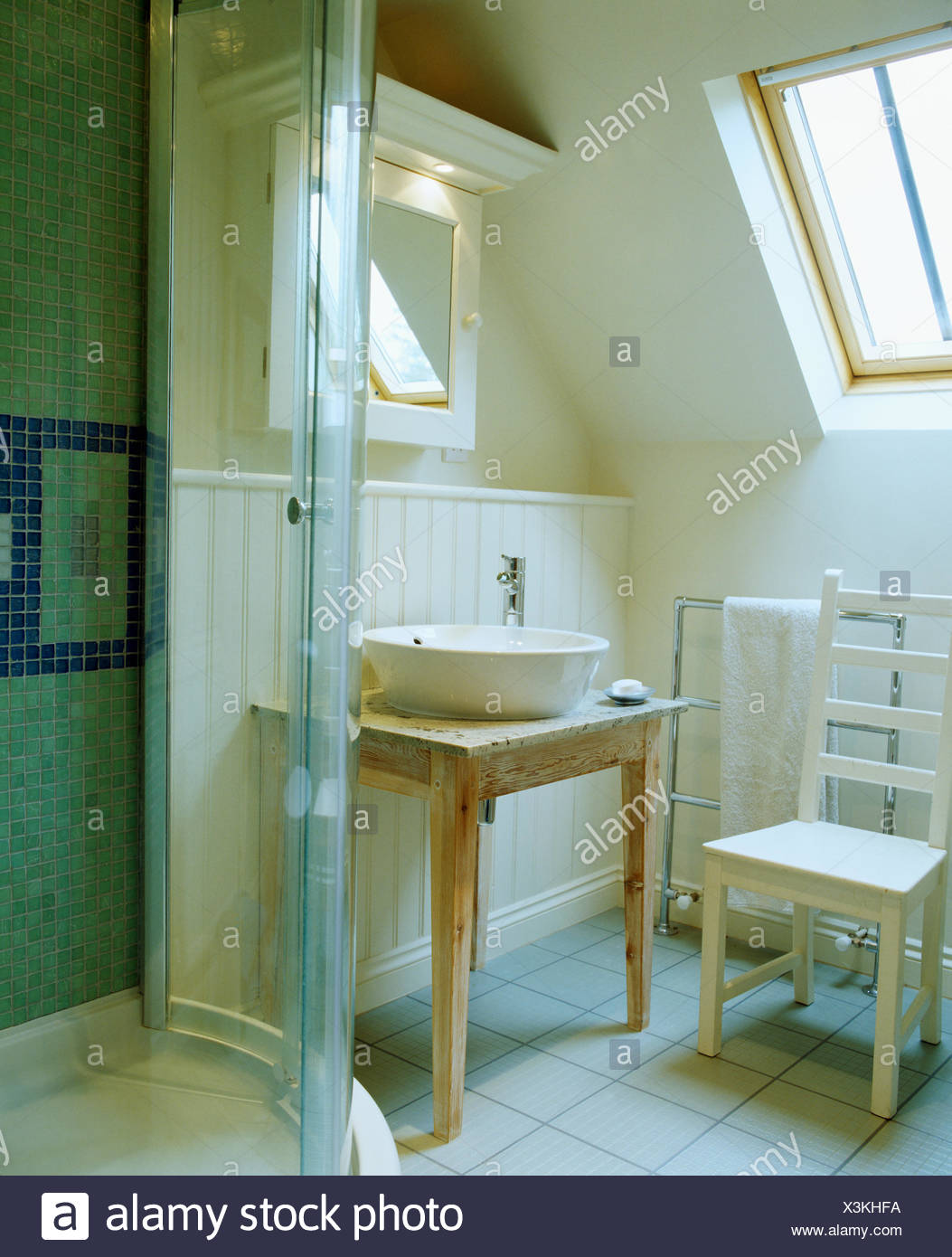 White bowl basin on wooden table in small attic bathroom with white ...