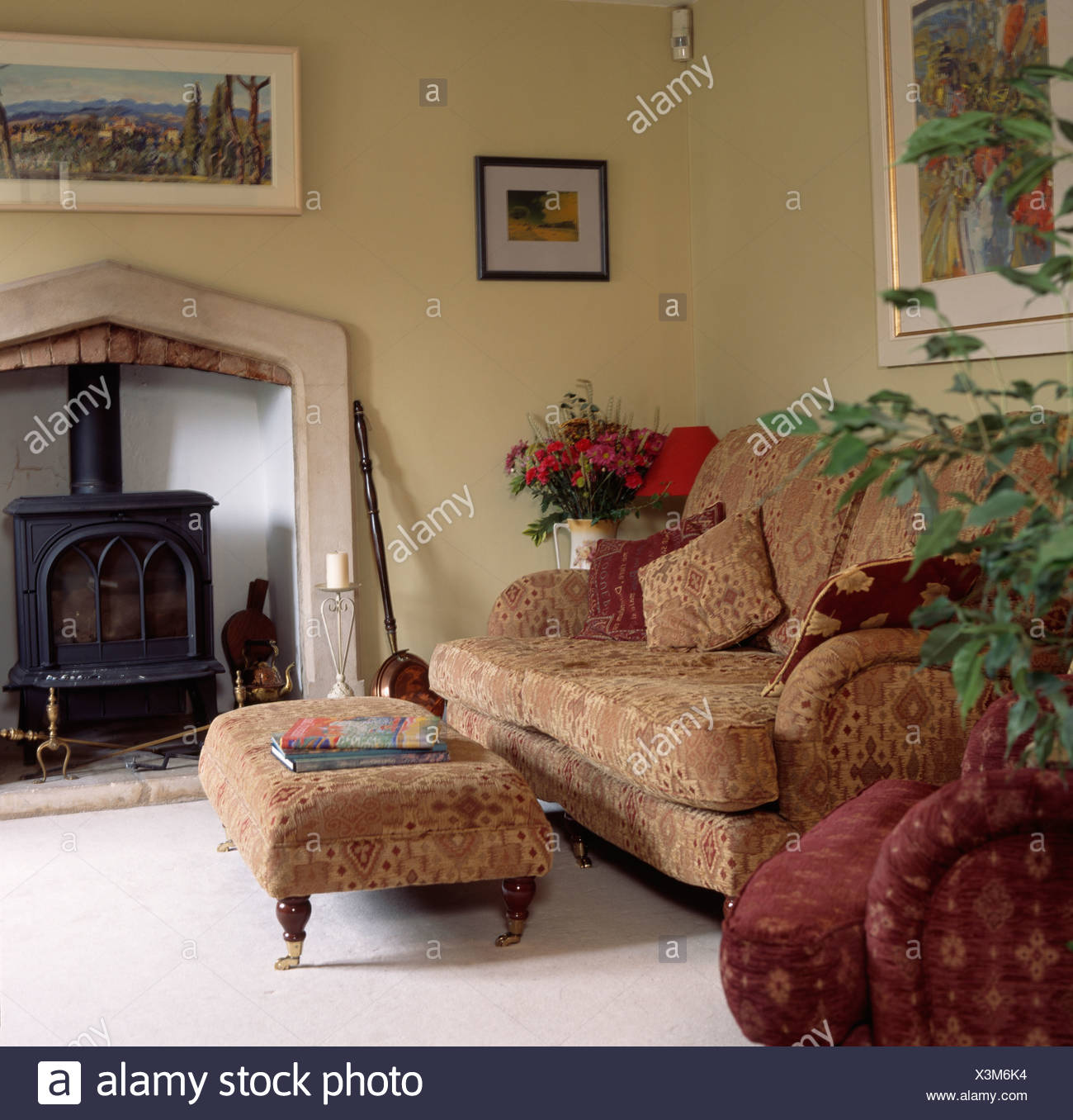 Superieur Patterned Neutral Sofa And Matching Upholstered Stool In Country Living Room  With Black Wood Burning Stove In Fireplace