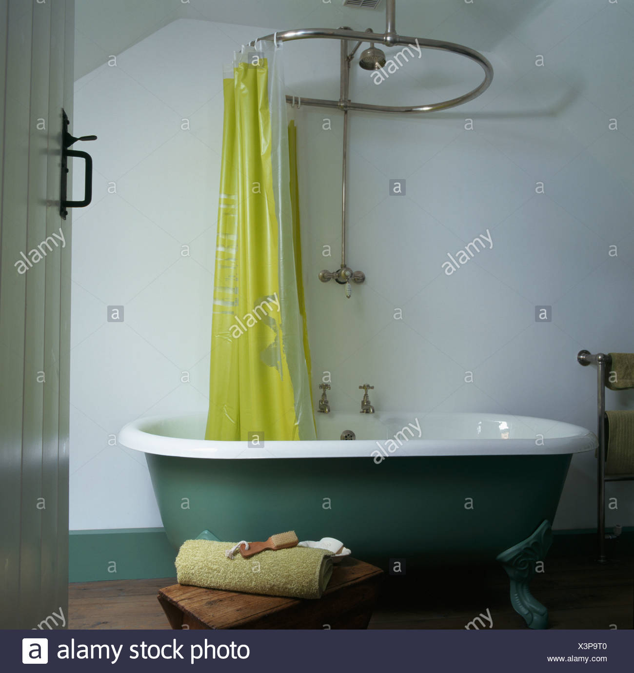 Yellow plastic curtain on chrome shower rail above green roll top ...