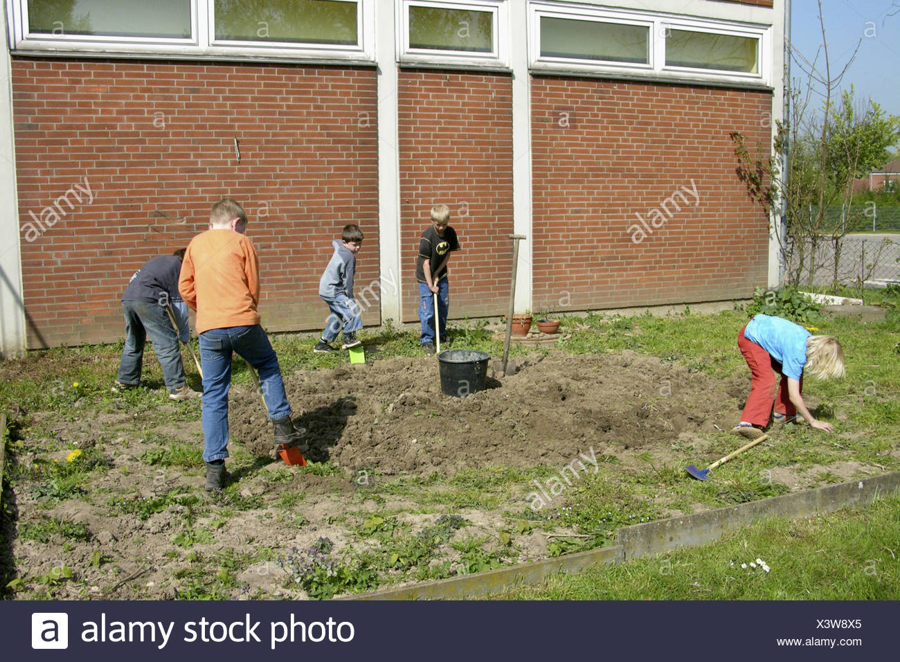 children burrowing the soil in the garden of a primary school to ...