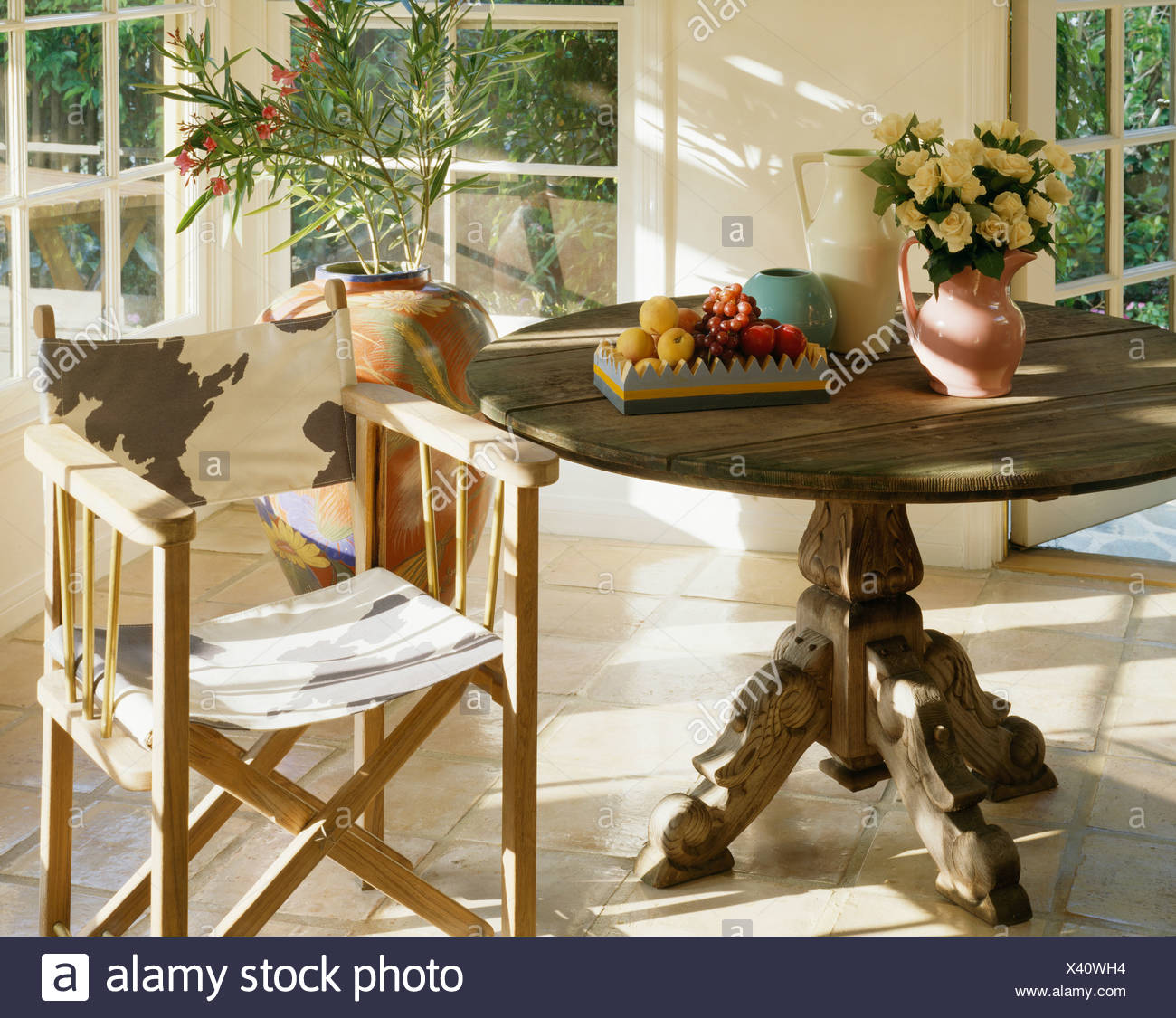 Close-up of circular antique table with animal-print director's chair in  sunny dining room - Close-up Of Circular Antique Table With Animal-print Director's